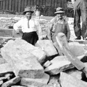 historical photo of workers near concrete pile