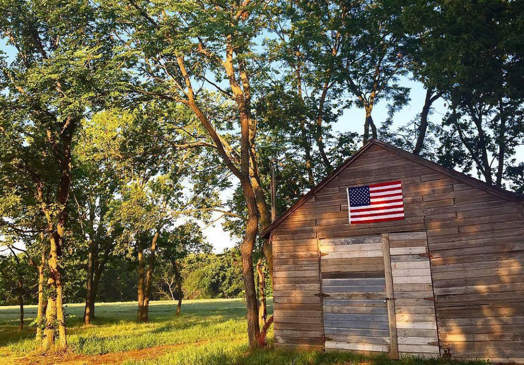 blacksmith shop with US flag and trees in background