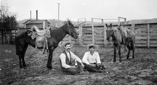 2 cowboys sitting on ground/two horses