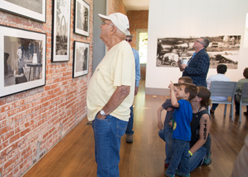 man and mother with children admiring photography exhibit of Otto Kratzer at the volland store