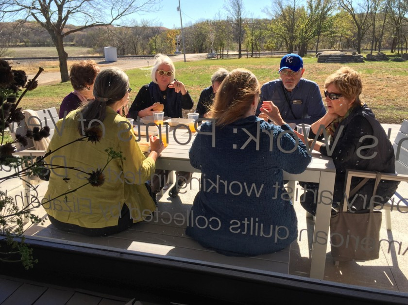 view-through-front-window-of-volland-store-of-group-picnicking-on-front-porch-in -sunshine