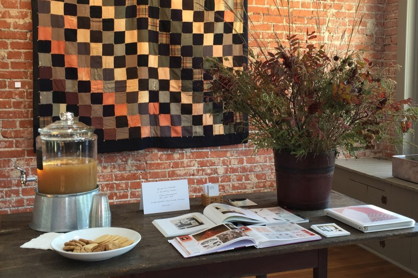 reception-table-with-cider-cookies-fall-arrangement-of-natural-grasses-and-books-about-exhibiting-artist-with-vintage-quilt-as-backdrop-